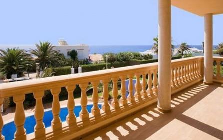 Blick von der Terrasse über den Poolbereich auf das Meer