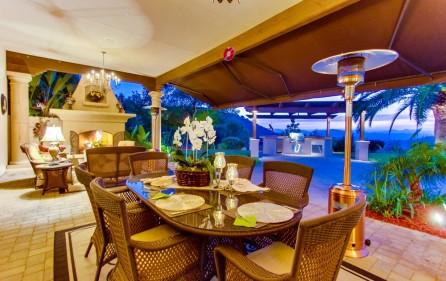 Veranda mit offenem Kamin und Blick auf den BBQ-Grill (bei Nacht)